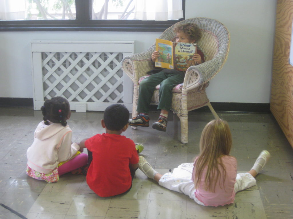 Kindergartener Reading to Younger Children